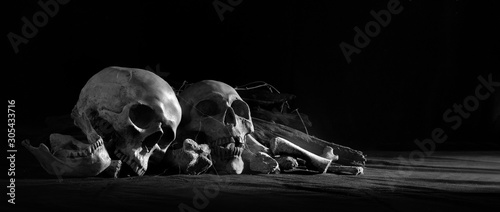 Fotomural Skulls with pile bone front dark background and on black cloth floor