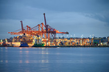 International Cargo Ship With Containers Cargo Illumination And Gantry Cranes At Port