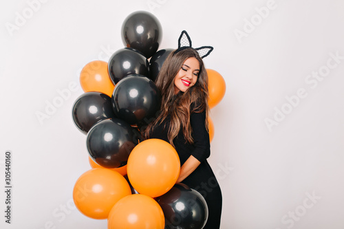 Fotografía  Shy long-haired woman posing with colorful halloween balloons