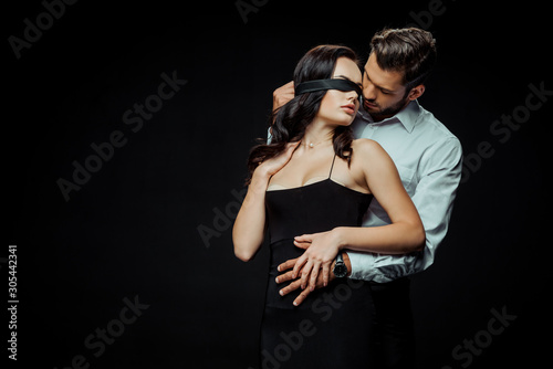 Fotomural  handsome bearded man looking at blindfolded girlfriend isolated on black