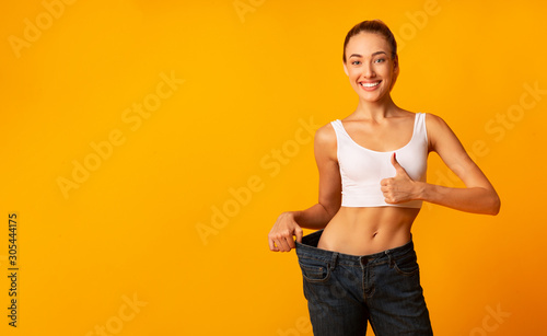 Photo Girl In Oversize Jeans Gesturing Thumbs Up Smiling, Yellow Background