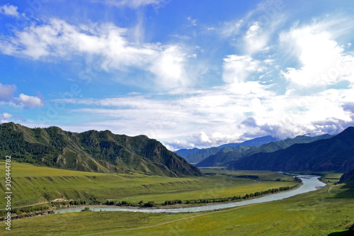 The sunny green valley of the Katun River is surrounded by mountains and hills Canvas Print