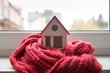 house in winter - heating system concept and cold snowy weather with model of a house wearing a knitted cap