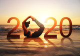 Happy new year card 2020. Silhouette of healthy girl doing Yoga Bow pose on tropical beach with sunset sky background, woman practicing yoga as a part of the Number 2020 sign.