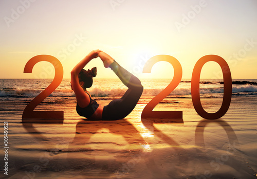 Happy new year card 2020. Silhouette of healthy girl doing Yoga Bow pose on tropical beach with sunset sky background, woman practicing yoga as a part of the Number 2020 sign. - 305450521