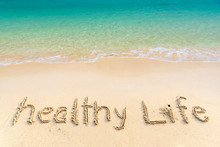 Healthy Life, Lettering On Golden Sand  Beach With Wave And Clear Blue Sea. Message Handwritten In Sand On Beautiful Beach. Healthy Life Sign On Holiday Vacation Concept For Background And Copy Space.