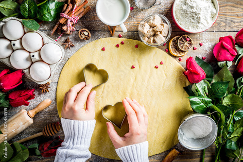 Fototapety, obrazy: Valentine day baking background. Ingredients for cooking Valentine's cookies. Flour, eggs, sugar on wooden background with red flower roses. Top view copy space. Female hands  with cookie cutters