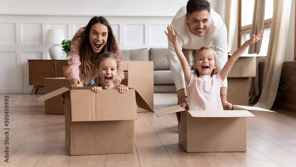 Excited family having fun on moving day riding in boxes