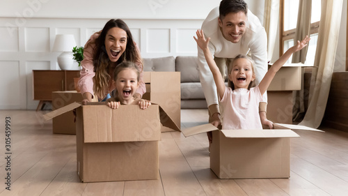 Wall Murals Equestrian Excited family having fun on moving day riding in boxes