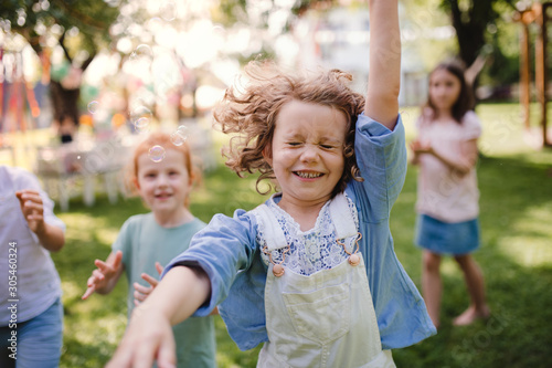 Small children standing outdoors in garden in summer, playing. Canvas Print