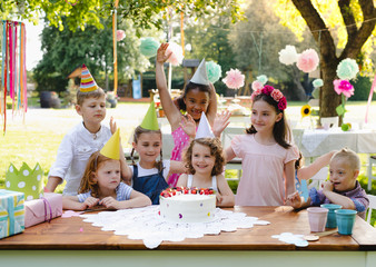 Down syndrome child with friends on birthday party outdoors in garden.