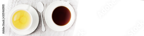 Recess Fitting Tea Two cups of black and green tea with cane and white sugar cubes on white. Top view. Half banner format. Wide panoramic image.