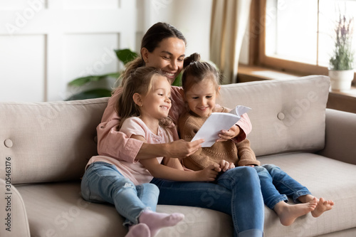 Fotografiet Happy young mother read book embrace little children daughters