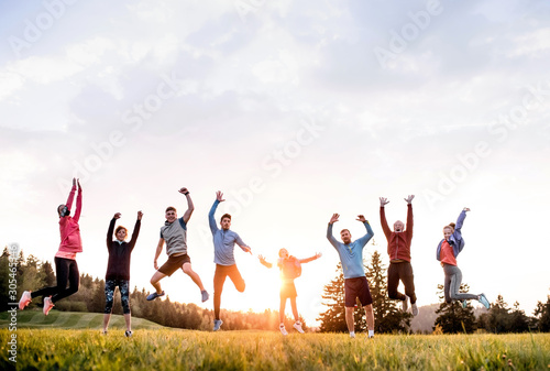 Large group of fit and active people jumping after doing exercise in nature Fototapet
