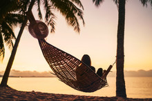 Young Woman Relaxing In Hammock Hinged Between Palm Trees On The Sand Beach At Orange Sunrise Morning Time