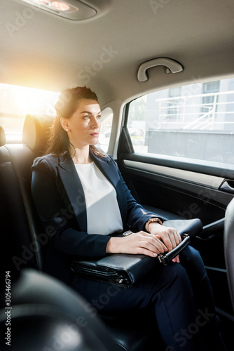 Photo selective focus of beautiful ambassador holding briefcase while sitting in car