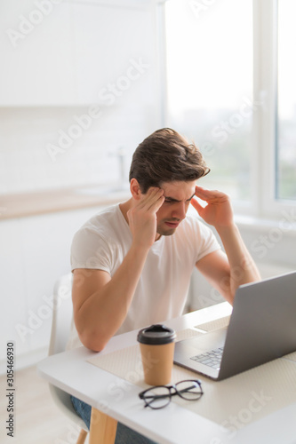Frustrated with problems young man working on laptop computer at home Canvas Print