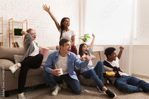 Obraz Emotional football fans. Teens watching match at home - fototapety do salonu
