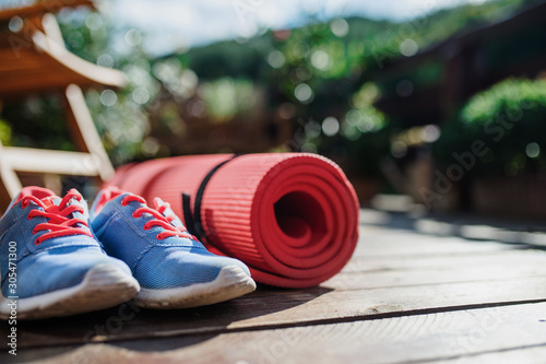 Obraz Exercise mat and trainers outdoors on a terrace in summer. - fototapety do salonu