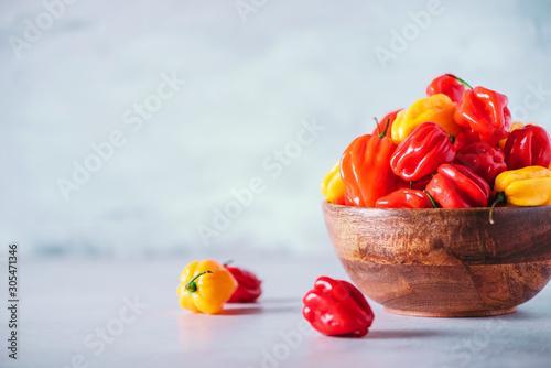 Obraz na plátně Colorful scotch bonnet chili peppers in wooden bowl over grey background