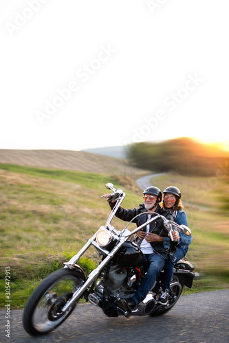 A cheerful senior couple travellers with motorbike in countryside. Wall mural