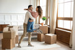 Leinwanddruck Bild - Happy husband lifting excited wife celebrating moving day with boxes