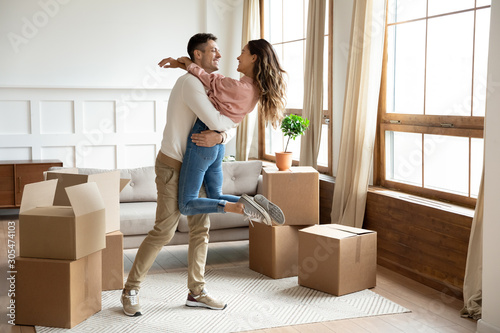 Obraz Happy husband lifting excited wife celebrating moving day with boxes - fototapety do salonu