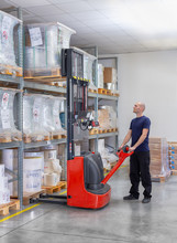 Warehouseman In Storehouse Moving Pallet With Electric Stacker. Worker In Warehouse Stacks Pallet In Rack System.Caucasian Labourer Working With Small Electric Forklift. Man With High Lift Pallet Jack