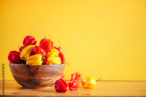 Colorful scotch bonnet chili peppers in wooden bowl over orange background Canvas Print