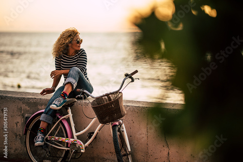 Adult caucasian woman enjoying outdor leisure activity relaxing after a ride on a vintage bike, sitting on a wall looking at the ocean -healthy active lifestyle people