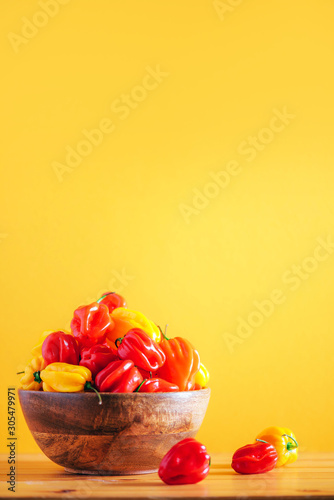 Colorful scotch bonnet chili peppers in wooden bowl over orange background Wallpaper Mural