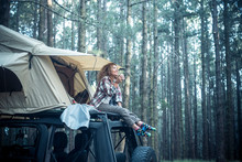 Happy Free Beautiful People Caucasian Woman Sit Down On The Roof Of The Car With Tent Mounted On It For Free Travel Camping Lifestyle - Wanderlust Vehicle To Enjoy The Nature And Vacation In Forest