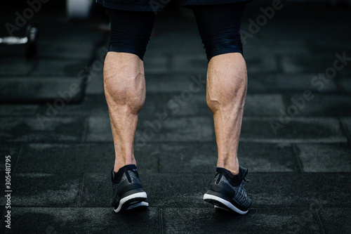 Photographie trained legs with muscular calves in sneakers in training gym during hard fitnes