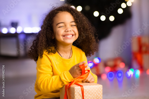 Happy african girl unwrapping her xmas gifts at home Fototapet