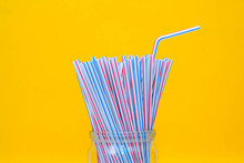 Plastic Straws In A Glass Jar With Yellow Background. Space For Text