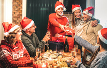 Friends Group Wearing Santa Hat Giving Each Other Christmas Presents - Champagne Wine Toast At Home X Mas Dinner - Holiday Concept With Young People Sharing Time Together And Having Fun On Winter Time