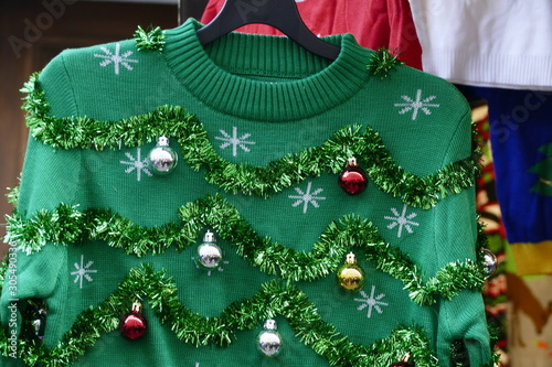 Valokuva Beautiful or ugly: green Christmas sweater with decor balls