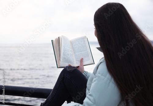 Valokuvatapetti Woman reading book near river on cloudy day