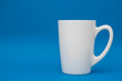 White ceramic cup on blue background. Space for text