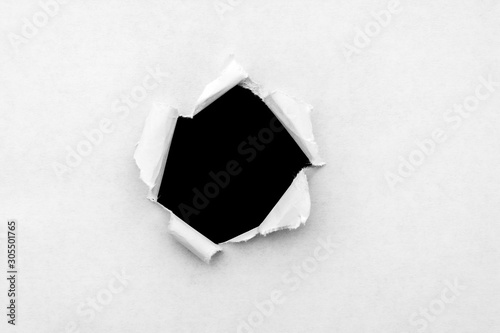 Fotografía A round hole in white paper with torn edges and a black isolated background inside