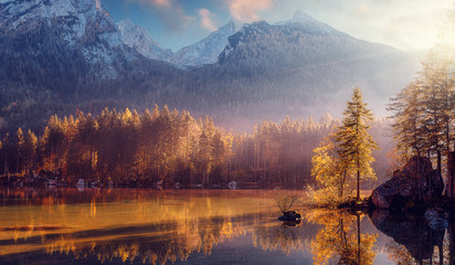 Fototapeta Vintage Awesome Nature Scenery. Beautiful landscape with high mountains with illuminated peaks, stones in mountain lake, reflection, blue sky and yellow sunlight in sunrise. Amazing nature Background.
