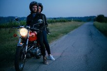 Portrait Of Young Couple On Vintage Motorbike At Roadside