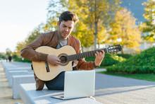 Man With Laptop Playing Guitar...