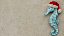 Turquoise Seahorse Wearing Santa Hat Close Up Isolated On A Festive Sandy Tan Background With Copy Space