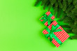 canvas print picture - Top view of fir tree branches and gift box on colorful background. Christmas time concept with empty space for your design