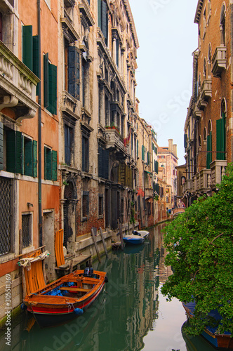 Fototapety, obrazy: Romantic and peaceful scene of Venice city. Medieval buildings reflected in turquoise water. Boats moored along the buildings. Famous touristic place and romantic travel destination. Venice, Italy