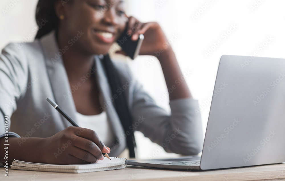 Fototapeta Black Businesswoman Taking Notes And Talking On Cellphone At Workplace