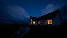 The Warm Glow Of Lit Rooms From A Remote Scottish Highland Croft, Bungalow At Dusk In Winter.
