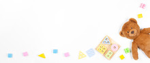 Baby Kids Toys Banner Background. Wooden Educational Geometric Stacking Blocks Shape Color Recognition Puzzle Toy, Teddy Bear And Colorful Blocks On White Background. Top View, Flat Lay