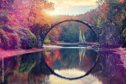 Awesome Autumn Landscape. Amazing sunset in Azalea and Rhododendron Park Kromlau. Rakotz Bridge, Rakotzbrucke Devil's Bridge in Kromlau, Saxony, Germany. Creative Artistic image. - 305514905